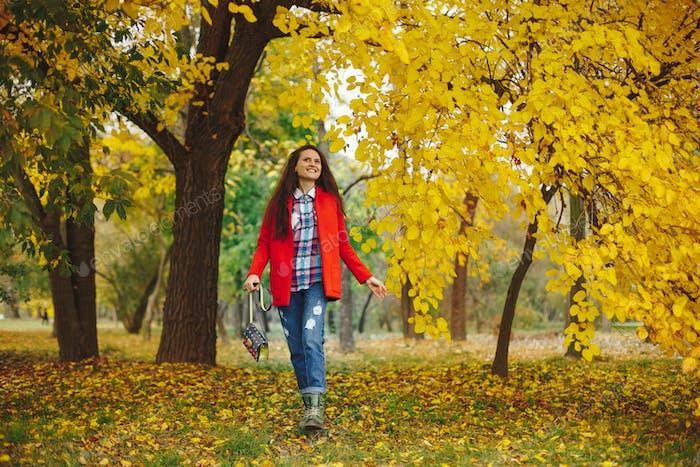 Mädchen mit langen welligen Haaren genießen Herbst im Park.