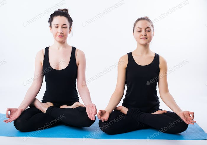Young man and woman doing yoga and meditating in lotus position isolated on white background.