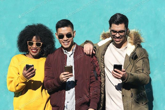 Gruppe von glücklichen Freunden mit dem Handy auf der Straße.