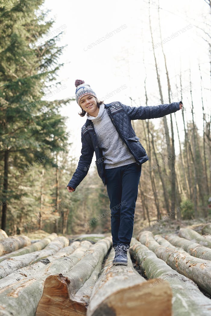 Happy teenage boy having a fun in the autumn forest