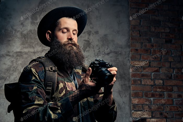 Handsome bearded traveler in a hat and camouflage jacket, with a backpack holds a photo camera