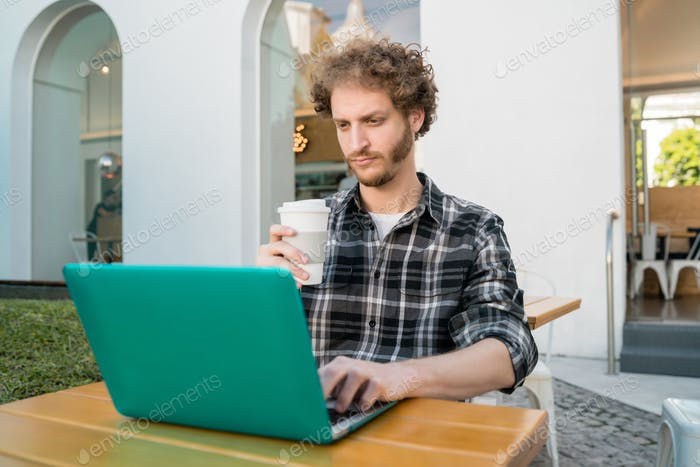 Young man using his laptop in a coffee shop.