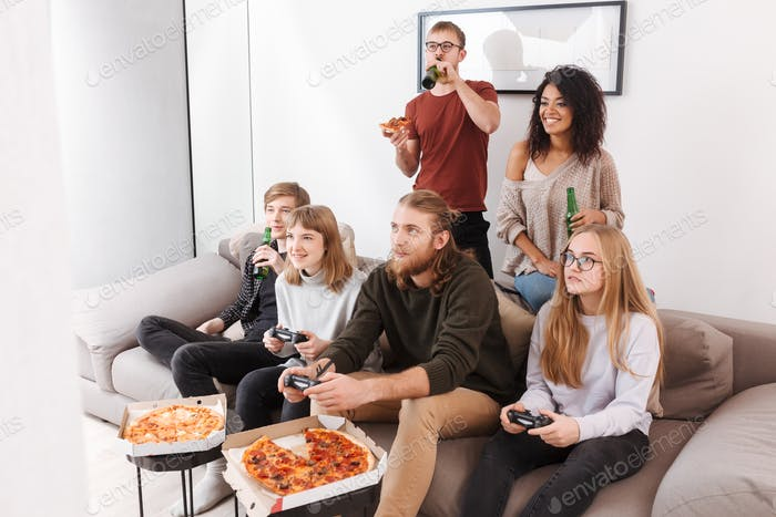 Group of smiling friends spending time together playing video games,eating pizza and drinking beer