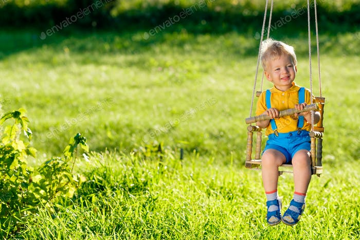Rural scene with toddler boy swinging outdoors.