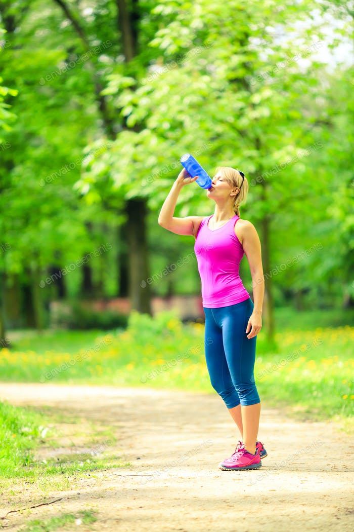 Woman runner drinking water on training
