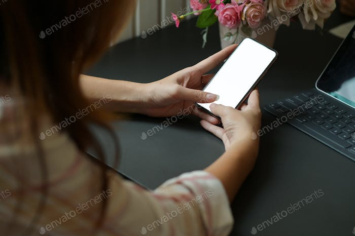 Young woman using a smartphone in hand to search for information and laptop on the desk in office.