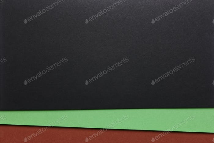 Colored cardboards background in black green brown tone. Copy space. Horizontal