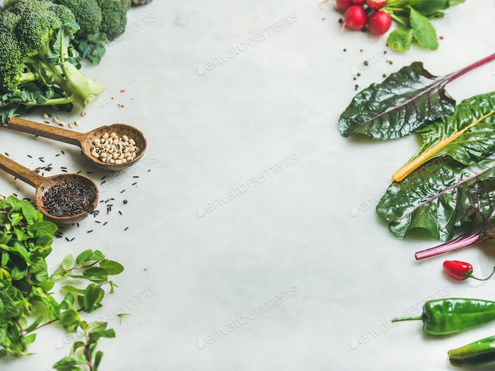 Fresh raw greens, vegetables and grains over marble countertop