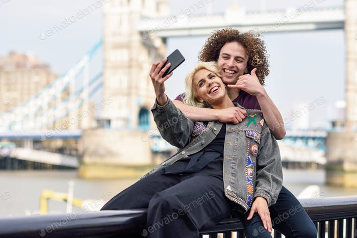 Young couple taking selfie photograph at the Tower Bridge