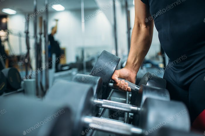 Male athlete takes heavy dumbbell in hand