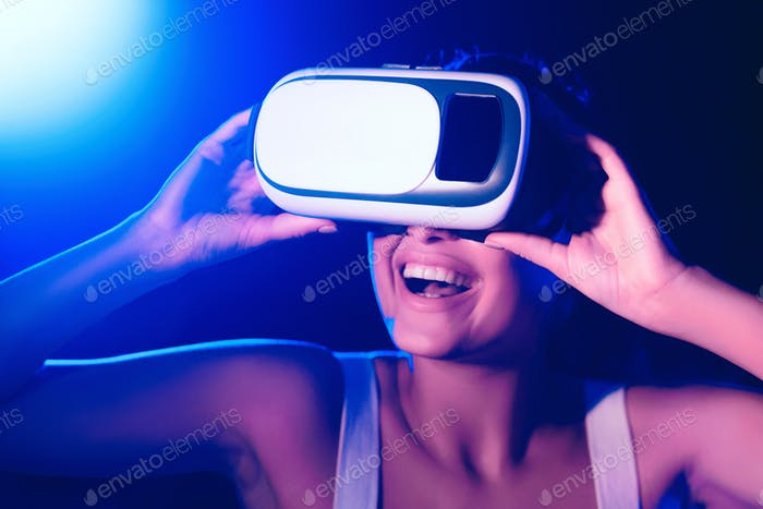Girl using VR goggles in colorful neon lights, having fun