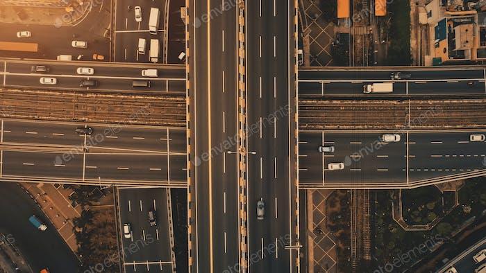 Солнце сверху вниз движения перекрестка дороги антенны. Городской транспорт с автомобилями, грузовиками, автобусами на солнечном свете