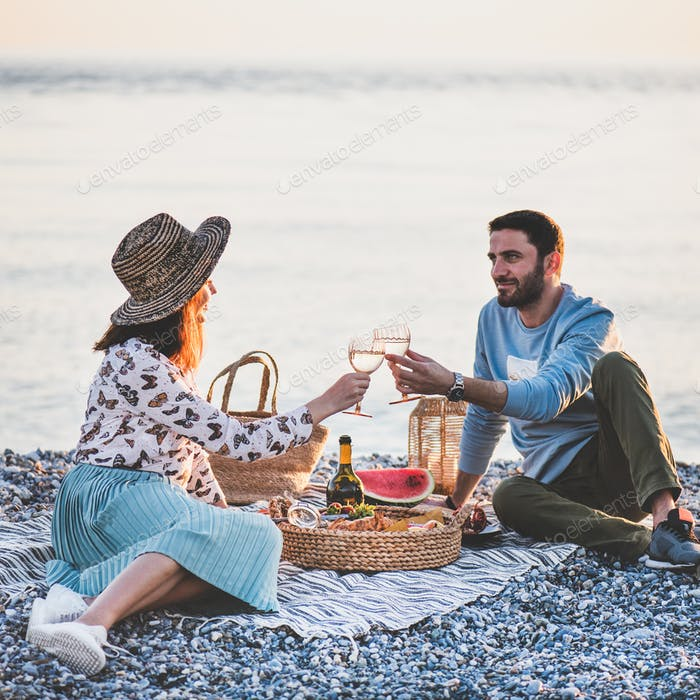 Young happy couple having picnic with sparkling, square crop
