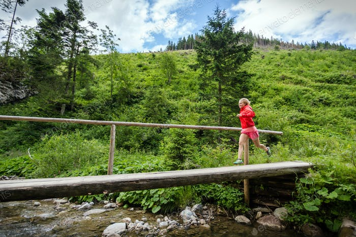 Young woman running on bridge in mountains on summer day