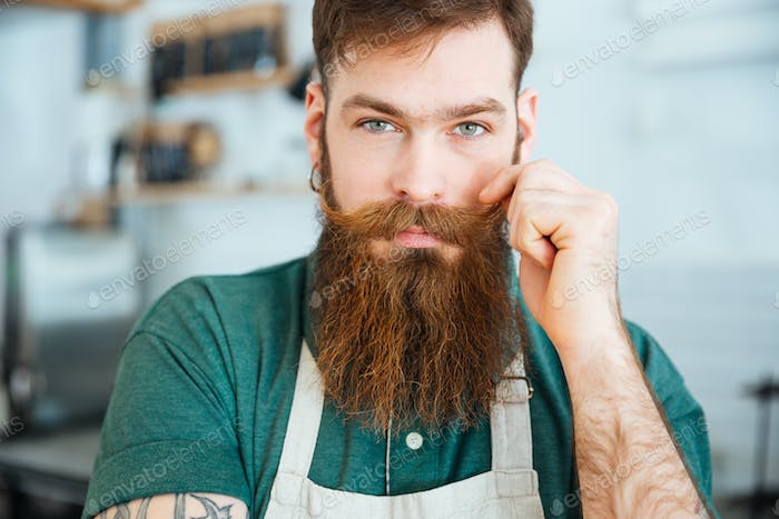 Handsome man with beard in white apron touching his moustache