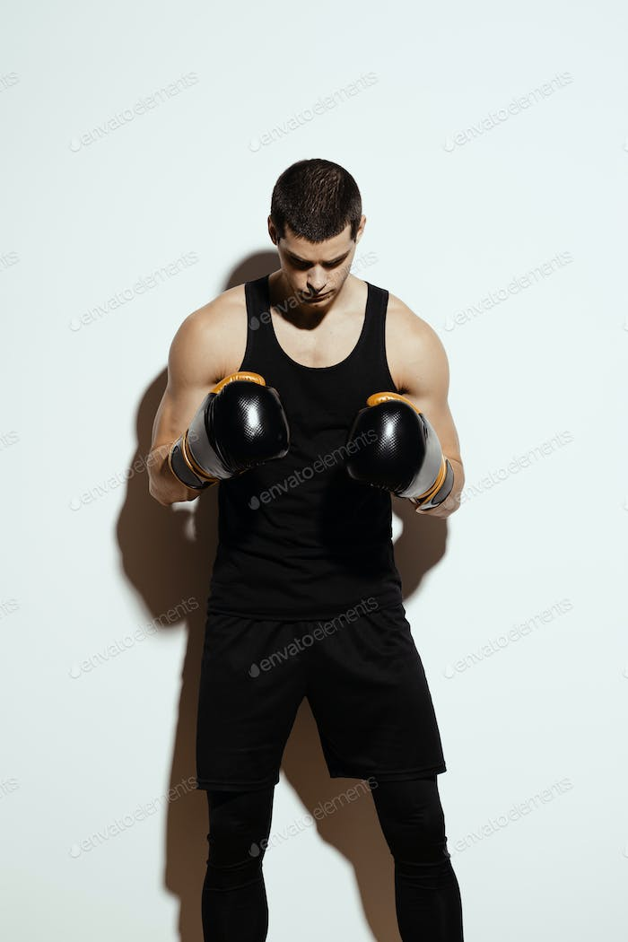 Tall attractive sportsman posing in boxing gloves over white background
