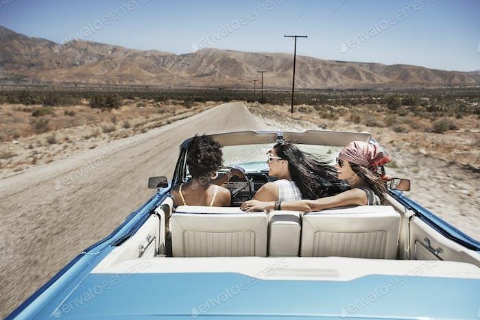 Drei junge Menschen in einem hellblauen Cabrio, fahren auf der offenen Straße über eine flache, trockene Ebene,