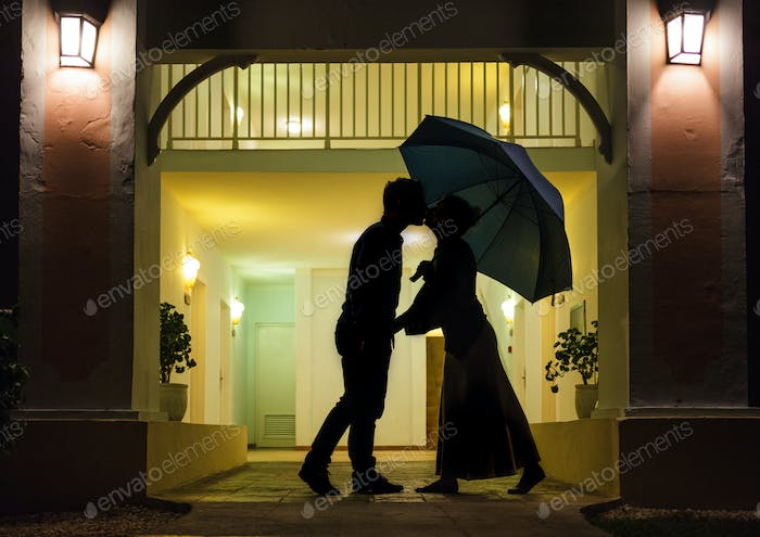 Couple in silhouette Kissing Under Umbrella