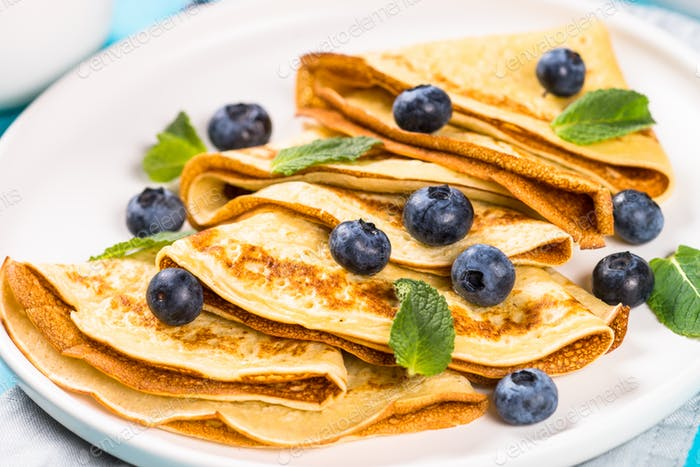 Crepes with blueberries at blue table