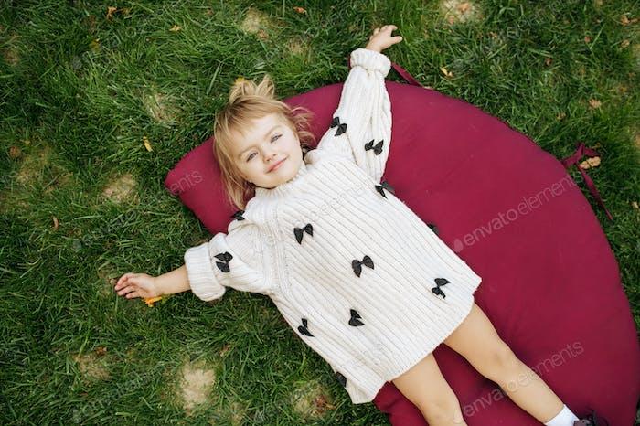 Little girl lying on the grass in the garden