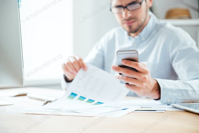 Cropped image of businessman using mobile phone in the office