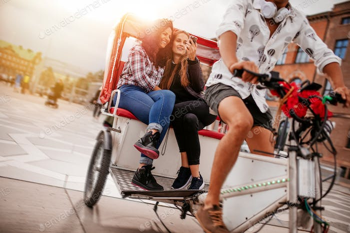 Teenage girls taking selfie on tricycle ride
