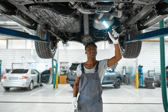 Male mechanic checks car suspension, auto service