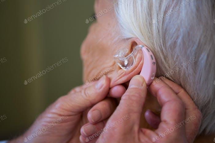 Arzt, das Hörgerät in das Ohr der älteren Patienten einführt