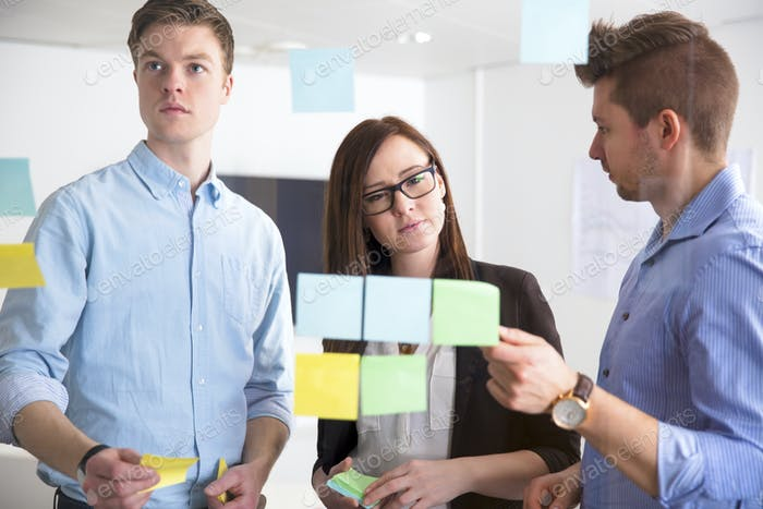 Business People Discussing Over Adhesive Notes Stuck On Glass
