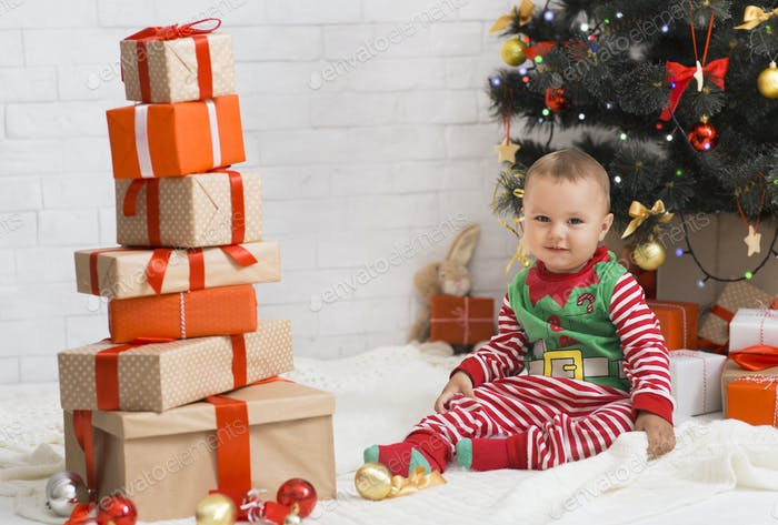 Adorable baby getting lots of gift boxes from loving family