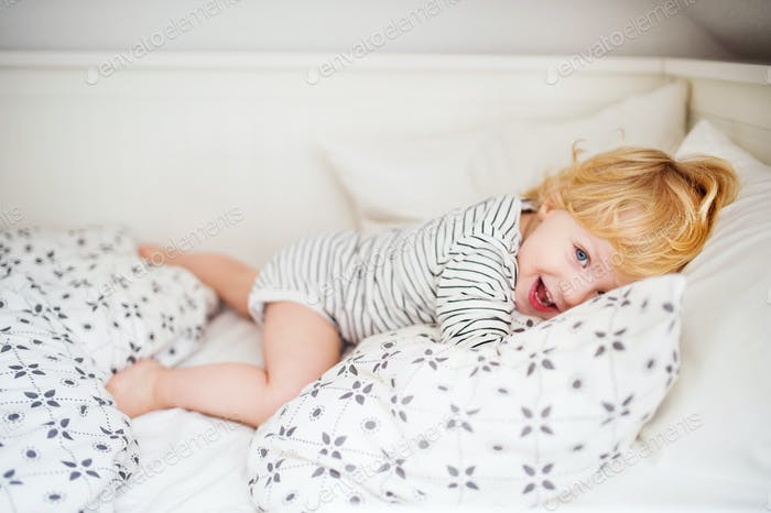 Cute toddler boy lying on bed at home.