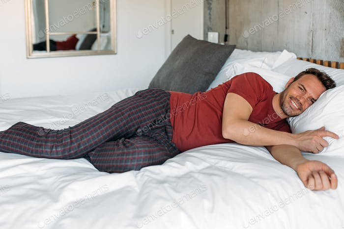 Beautiful man lying down on bed resting