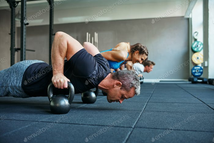 Fit people doing pushups together in a health club class