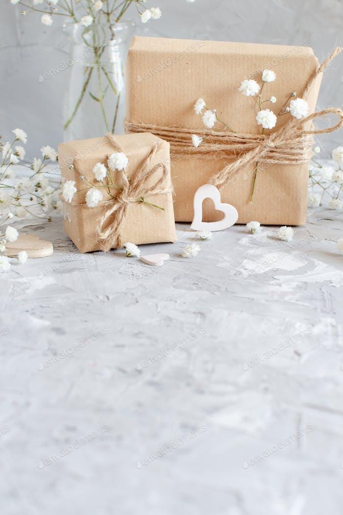 Geschenkboxen mit kleinen weißen Blumen