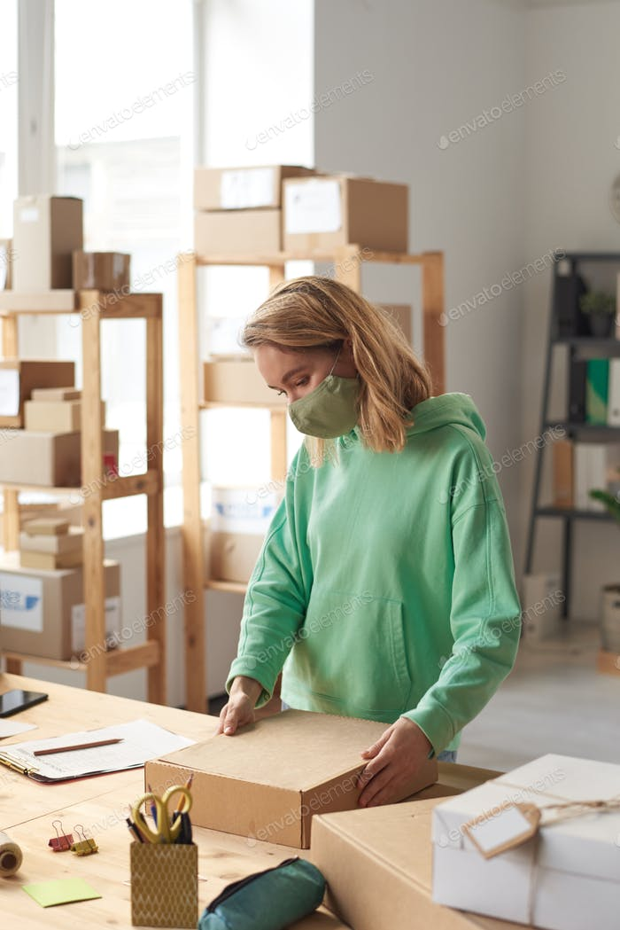 Woman with parcel in workshop