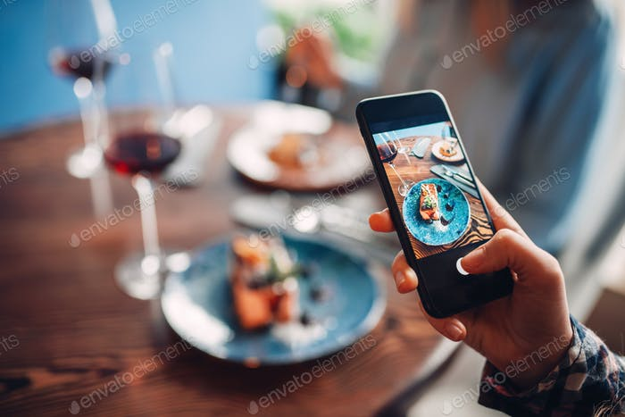 Female person makes shot of red wine and dessert