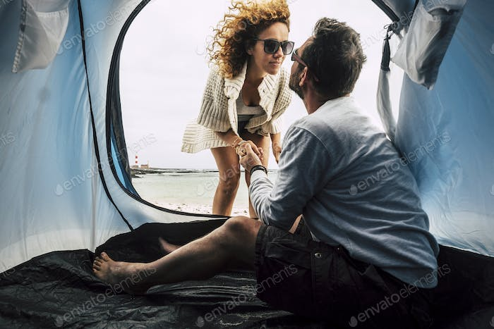 couple of caucasian woman and men 40 years old in love camping tent