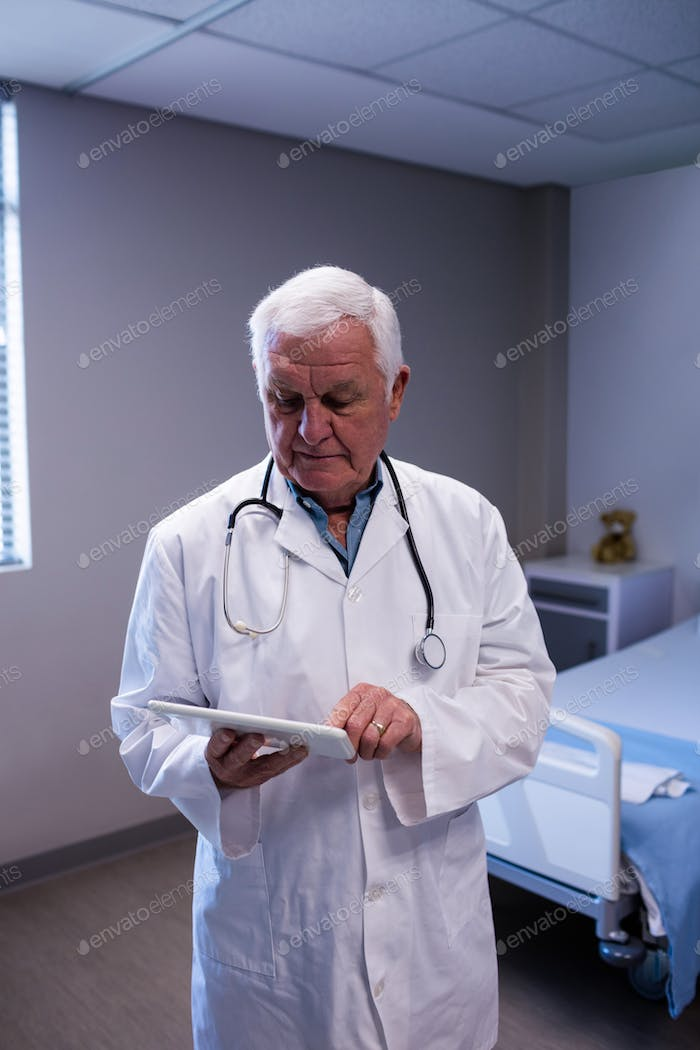 Male doctor using digital tablet in ward