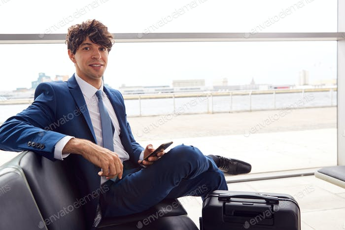 Portrait Of Businessman Sitting In Airport Departure Lounge Using Mobile Phone
