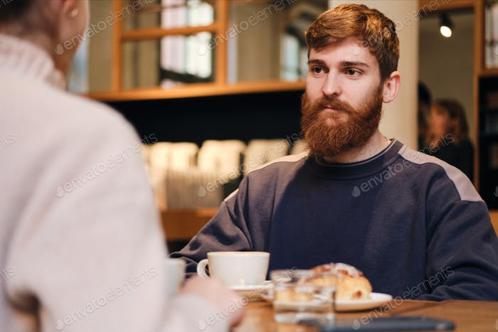 Young attractive man intently looking at girlfriend during coffee break in cafe