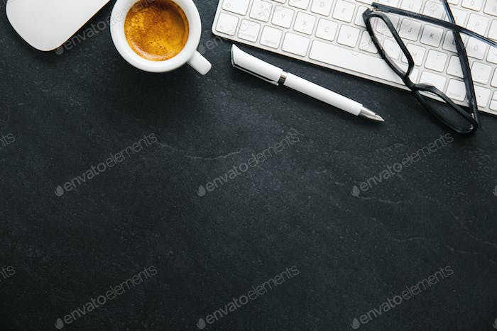 Office table with cup of coffee, keyboard and notepad