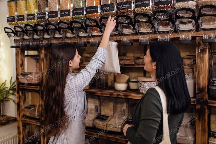 Shopkeeper assisting customer in packaging free shop.