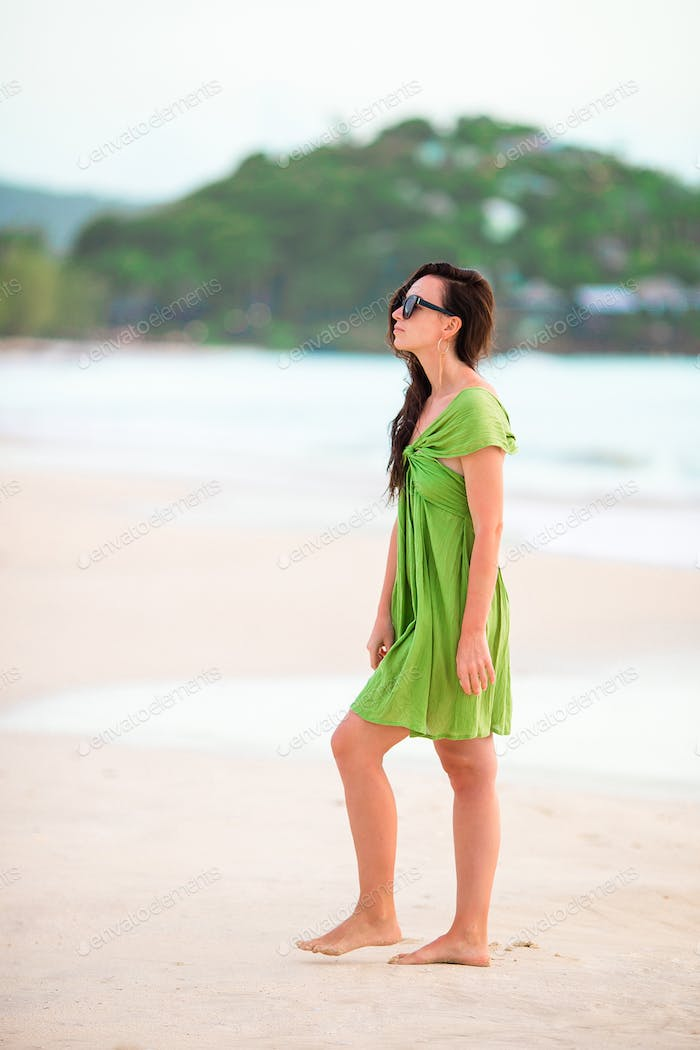 Young beautiful woman having fun on tropical seashore. Happy girl walking at white sand tropical