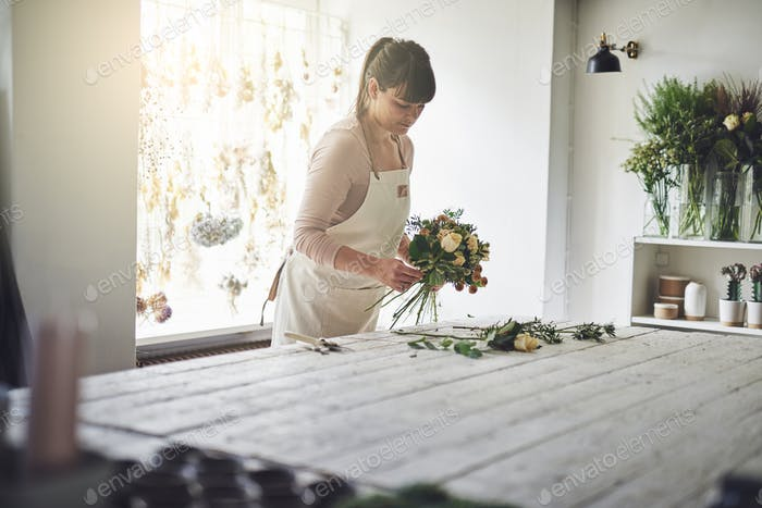 Florist making flower arrangements at a table in her shop