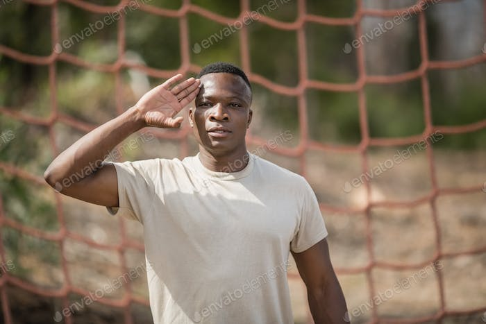 Military soldier giving salute during obstacle course