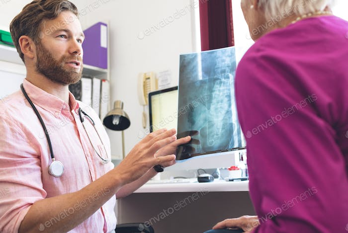 Male doctor showing x ray report to female senior patient in clinic