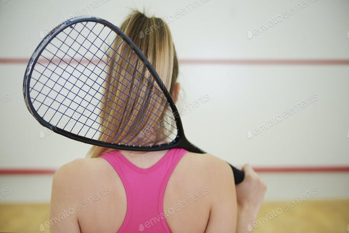 Rear view of squash or tennis player with racket