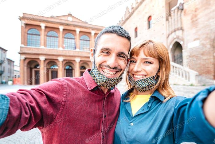 Happy boyfriend and girlfriend in love taking selfie with face masks