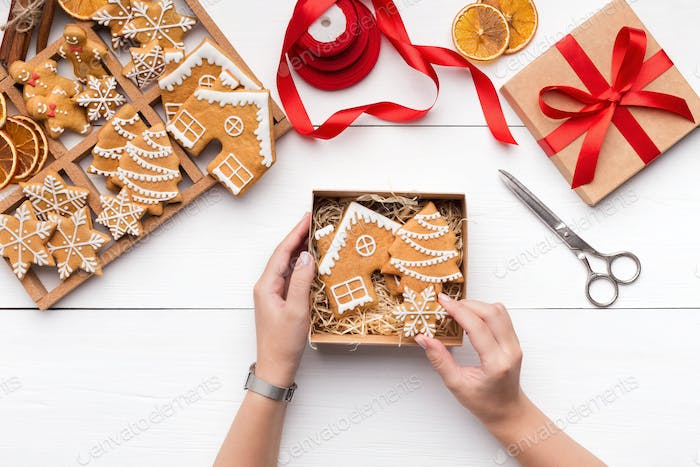 Woman packaging Christmas gingerbread cookies into gift box