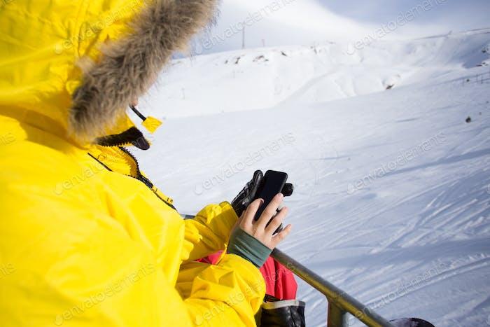 Snowboarder auf Skilift benutzen Smartphone